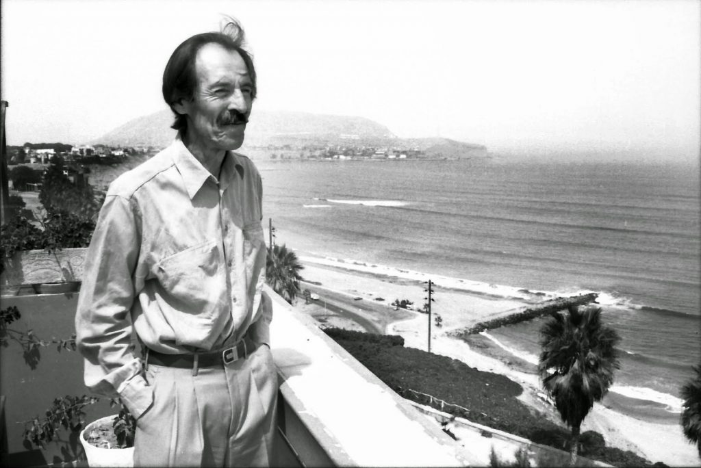 escritor julio ramón ribeyro posa numa cidade à beira-mar