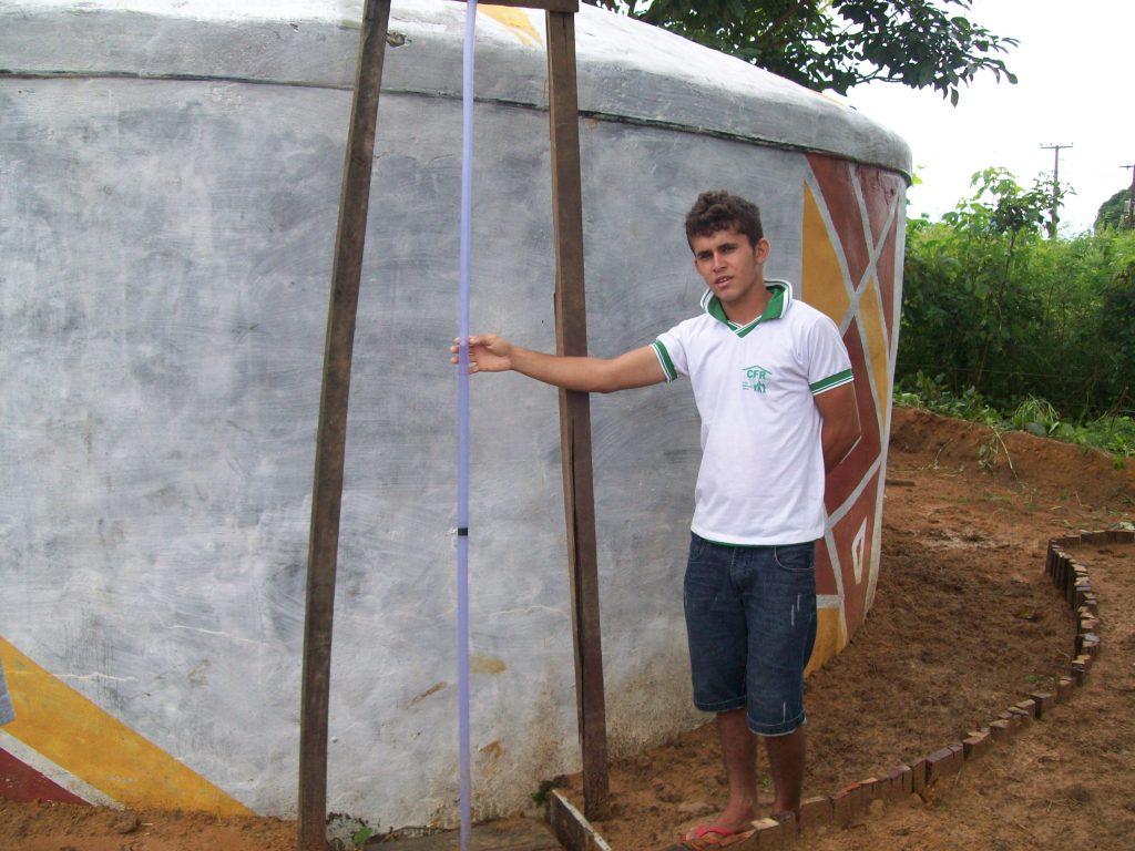 menino se apoia em caixa d'água que ajudou a construir