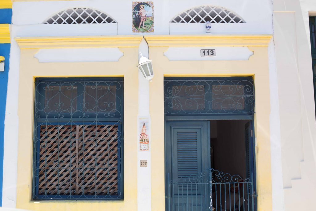fachada de casa branca e de portas azuis