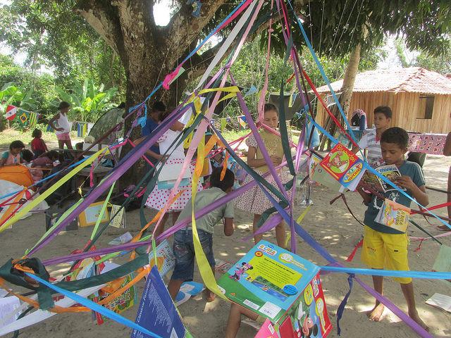 crianças leem livros e brincam com fitas no centro do quilombo narcisa no pará