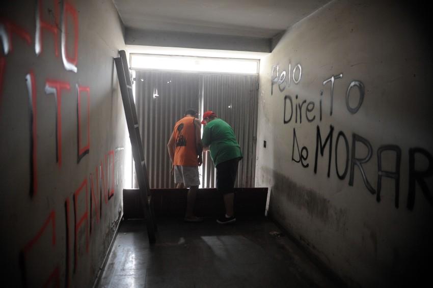 pessoas fecham as portas de uma ocupação