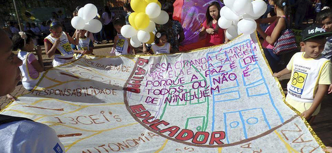 crianças seguram cartaz que diz bairro educador
