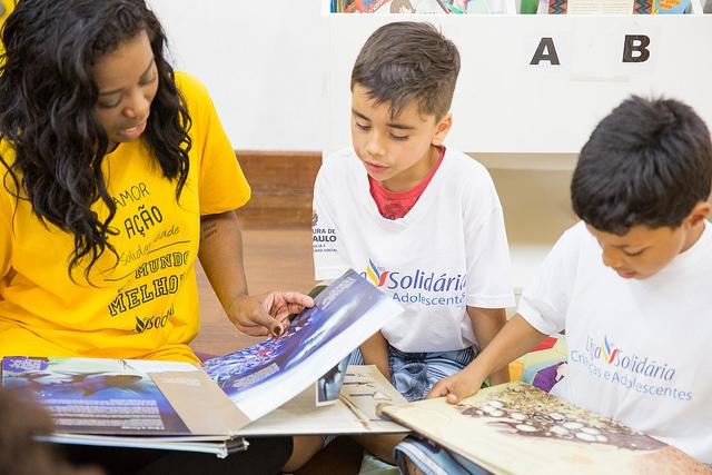 criança lê junto com voluntária na liga solidária