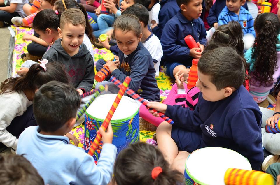 crianças brincam com instrumentos recicláveis