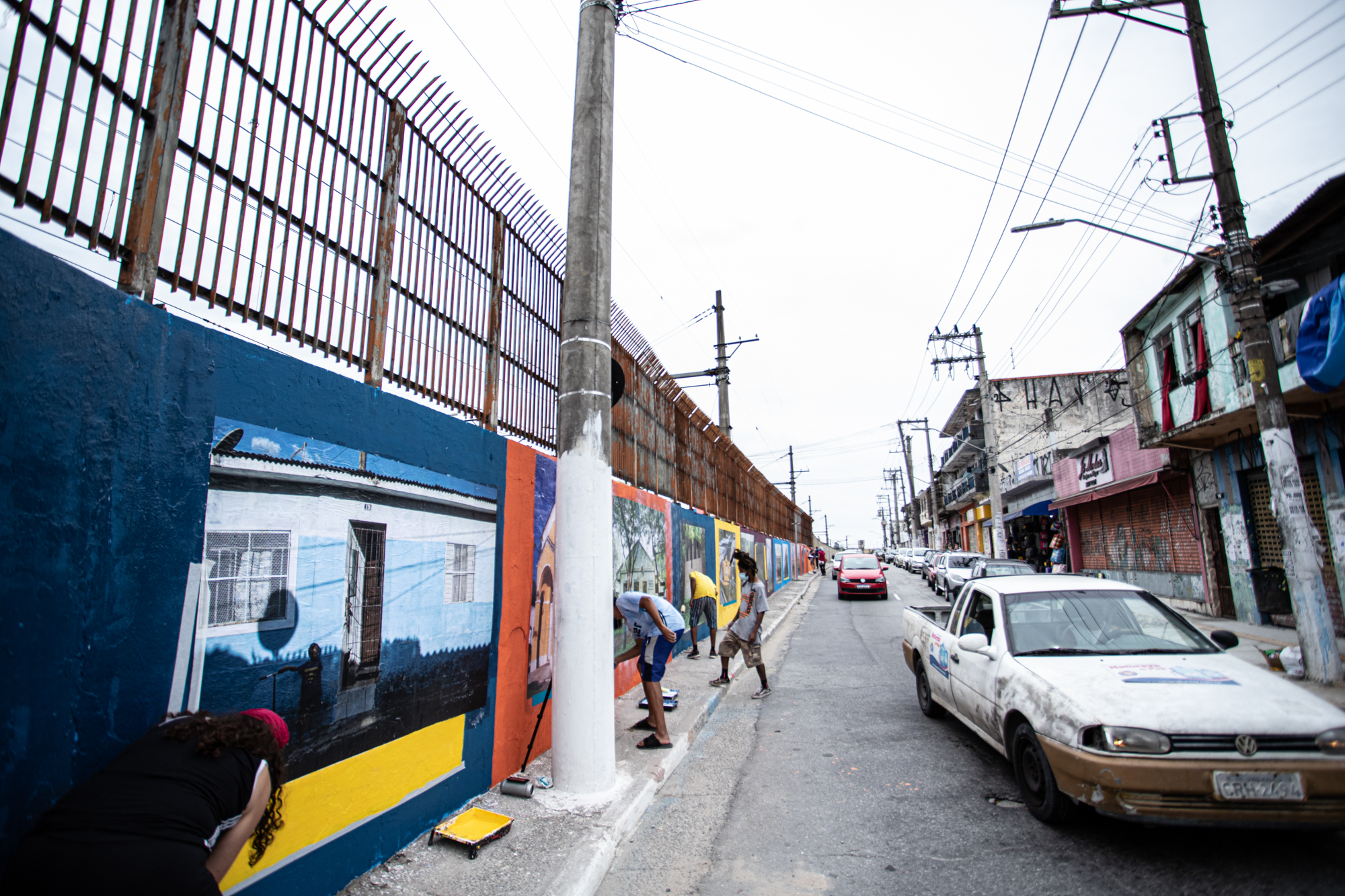 integrantes do CPDOC Guaianás colando os lambes no muro