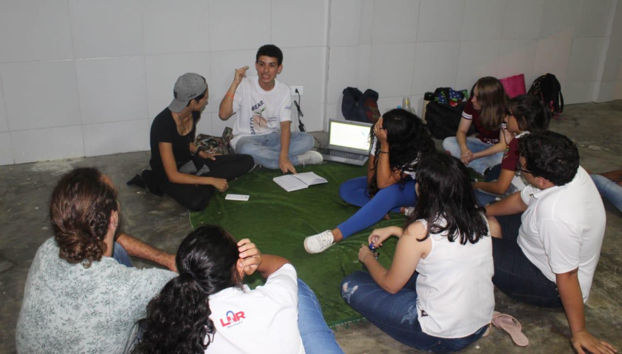 essa foto tem jovens sentados em círculos. Eles estão fazendo o planejamento do projeto arbo.