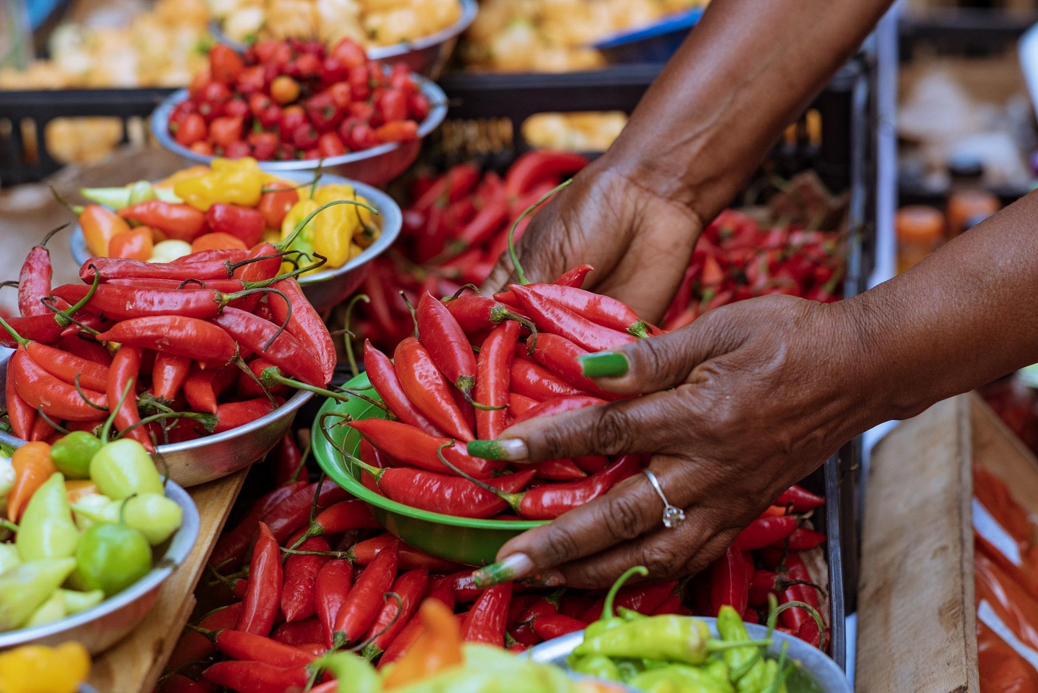 mercadora arruma pimenta e outras mercadorias no mercado da Vila Rubim
